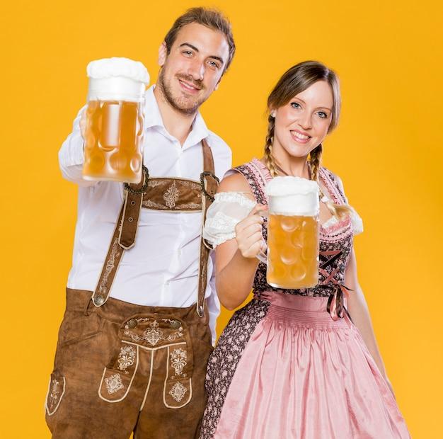 Oktoberfest pareja sosteniendo jarras de cerveza