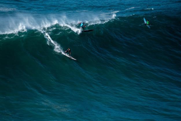 Ola alta del océano atlántico llevando a los surfistas hacia la costa de nazaré, portugal