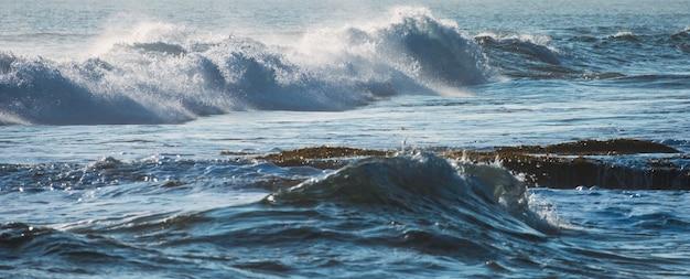 Ola azul con burbuja golpeando en la costa en el mar tropical