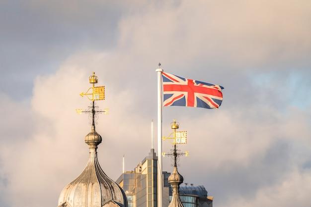 Ola británica ondeando en el cielo con una veleta en una iglesia
