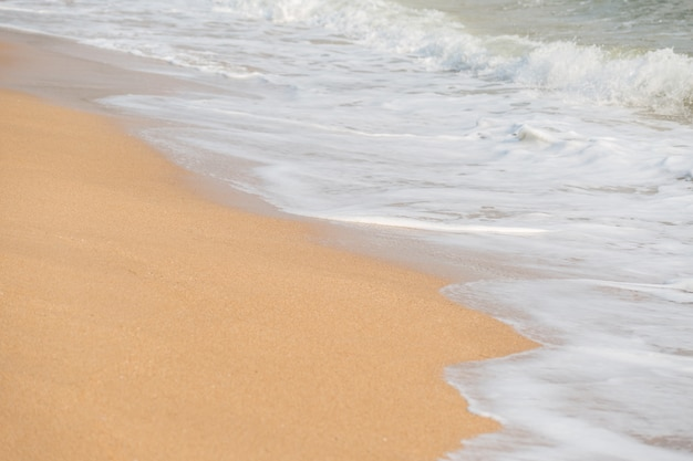 Ola de espuma suave y mar en el fondo de la playa de arena