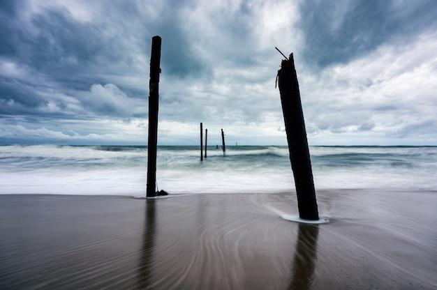 Ola grande golpeando un puente de madera decadente en la playa en un clima tormentoso en la playa de pilai, phang nga, tailandia