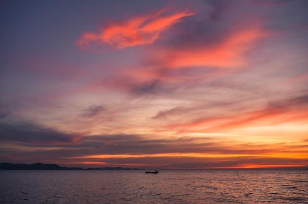 Ola hermosa del mar tropical con barco de madera y cielo colorido al atardecer