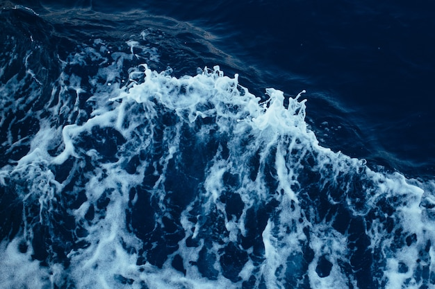 Ola de mar arremolinándose desde un bote a motor
