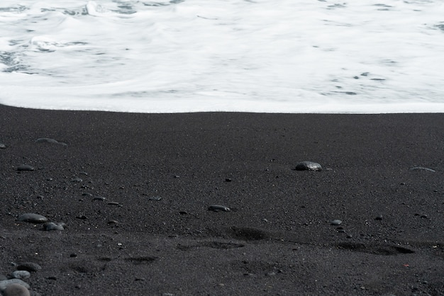 La ola oceánica con espuma blanca rueda sobre la playa de arena negra con guijarros.