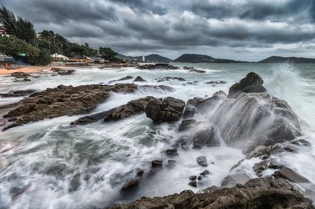 Ola oceánica rompiendo en las rocas en la costa en tormentoso en el mar tropical