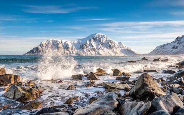 Ola del océano ártico golpeando las rocas con la montaña sol