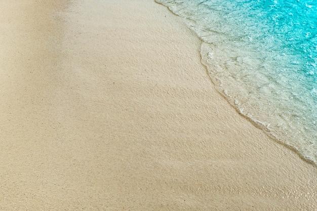 Ola del océano azul en la playa de arena con espacio de copia