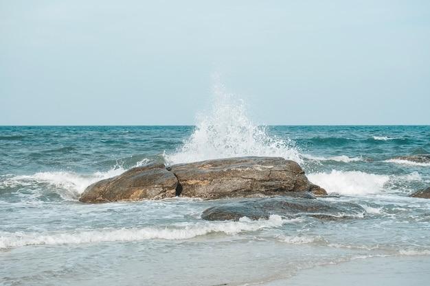 La ola y las salpicaduras del mar golpean la piedra en la playa de hua hin, prachuap khiri khan, tailandia. tono pastel