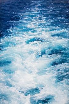 Ola traza colas de lancha rápida sobre una superficie de agua azul en el mar