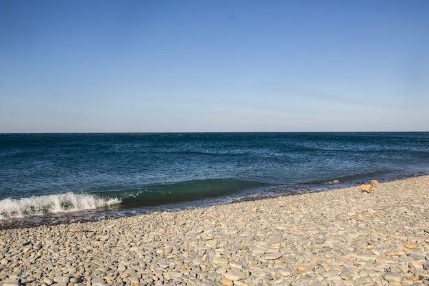 Las olas espumosas del mar en una playa de guijarros vacía