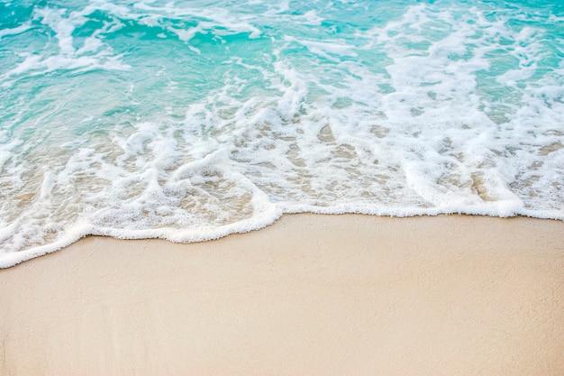 Olas espumosas en una playa de arena con agua de mar azul en una playa tropical