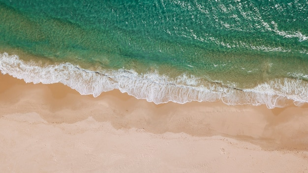 Olas espumosas y playa de arena desde arriba.