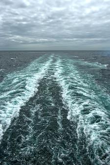 Olas espumosas en la superficie del agua detrás del crucero.