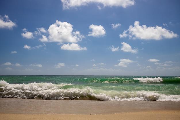 Olas fuertes en la hermosa playa de arena con cielo azul nublado