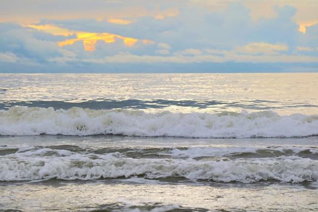 Las olas golpean en la playa con cielo anaranjado y nubes blancas en el mes.