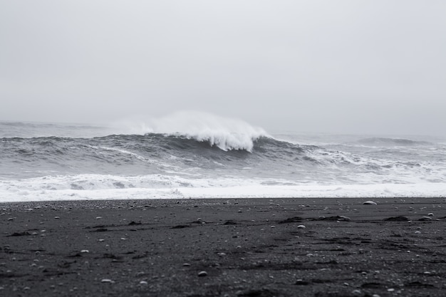Olas en la hermosa playa de arena negra volcánica en islandia.