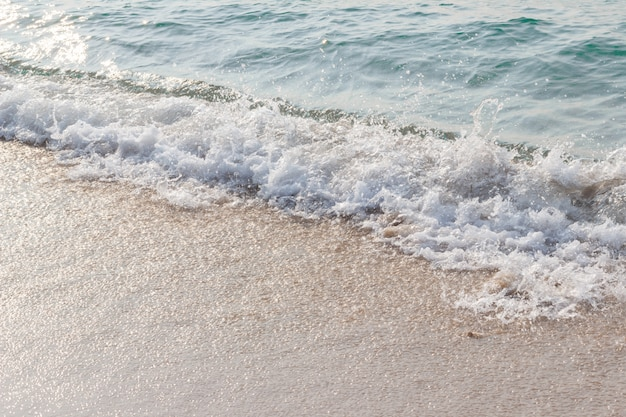 Las olas del mar golpean la playa, la luz cae sobre la superficie del mar.