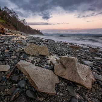 Olas oceánicas rompiendo en la costa durante el atardecer