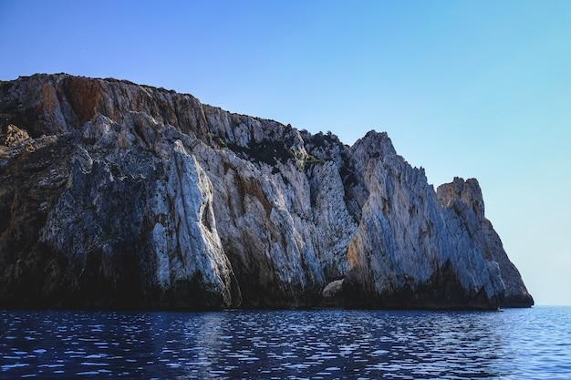 Olas del océano rodeadas por acantilados rocosos que brillan bajo el cielo azul