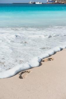 Olas del océano tocando las huellas de los pies en la playa tropical.