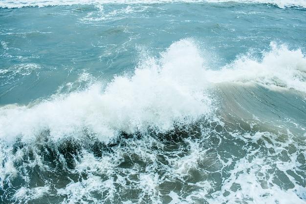 Olas rompiendo y rociando en alta mar y vientos fuertes. tormenta en el mar en otoño nublado día lluvioso.