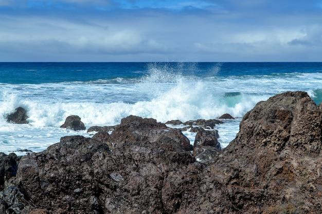 Olas sobre una roca negra en medio del mar