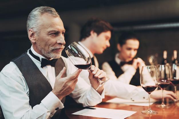 Old sommeliers está probando vino en el restaurante