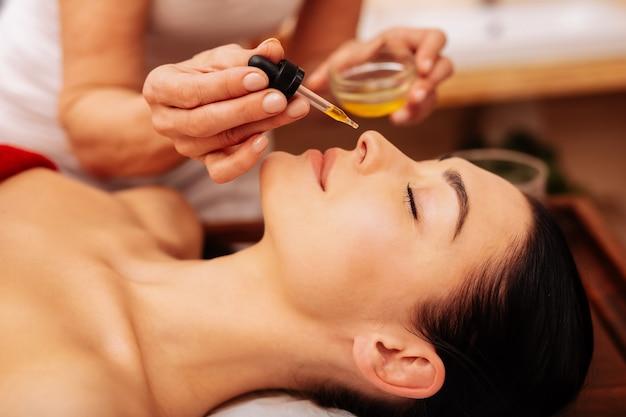 Oler y absorber. mujer hermosa de cabello oscuro acostado con los ojos cerrados y oliendo aceite perfumado mientras el trabajador lo mueve a la nariz