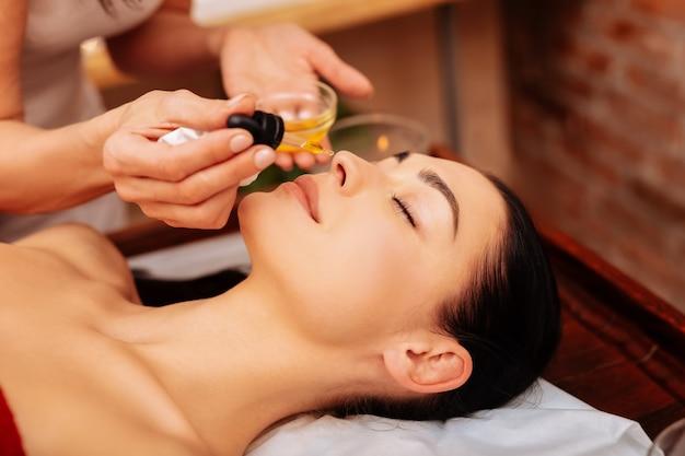 Oler aceite perfumado. trabajador profesional cuidadoso acercando el gotero a la nariz de su cliente en reposo