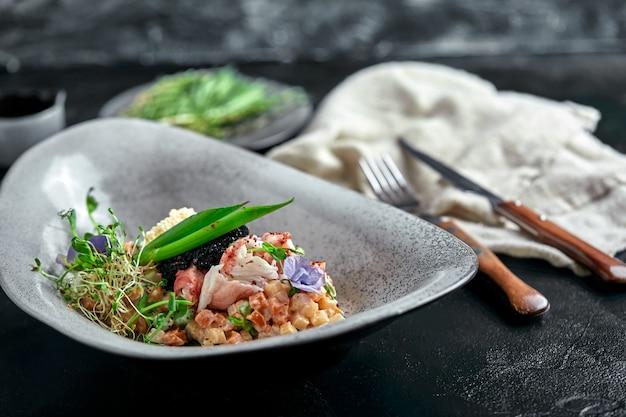 Olivier con carne de cangrejo en un hermoso cuenco en forma de ostras, en un oscuro.