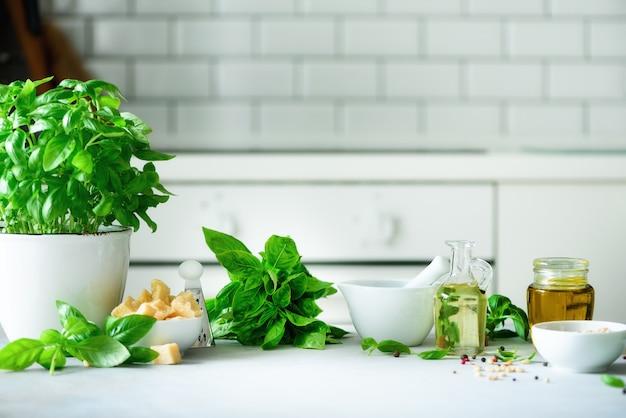 Olla de albahaca fresca, aceite, piñones, con fondo blanco de cocina.