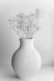 Olla de barro blanco con flores.