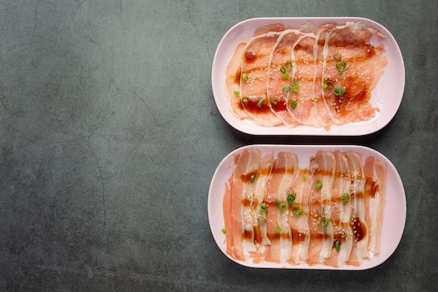 Olla caliente shabu; carne de cerdo fresca cruda en rodajas en un plato