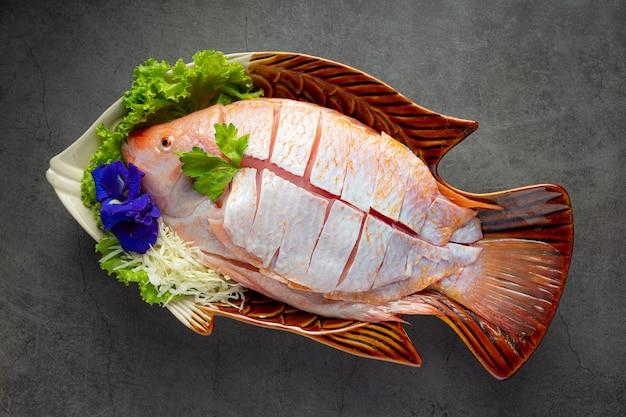 Olla caliente shabu; pescado fresco crudo en rodajas en un plato