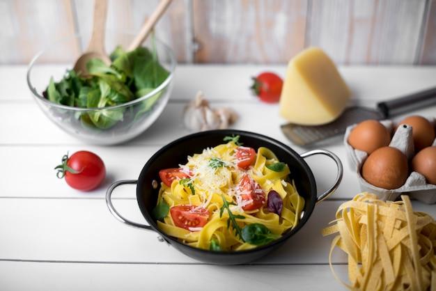 Olla de cocción rellena de pasta e ingredientes de tallarines saludables en una mesa de madera blanca