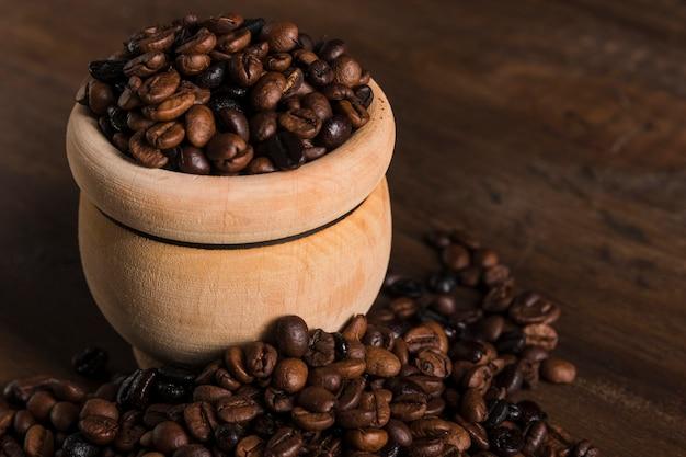Olla con granos de café en la mesa