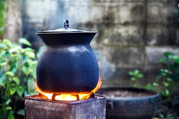 Olla de hierro al aire libre hervida en llamas de carbón