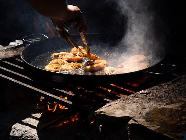 Olla irreconocible volteando camarones asados en una sartén con pinzas