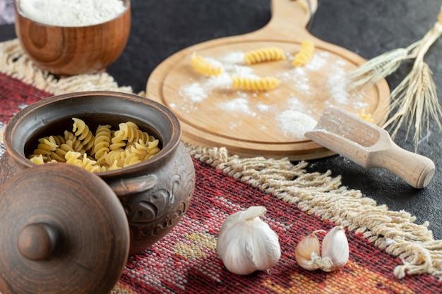 Una olla pequeña de macarrones en espiral sin preparar con ajo y harina.