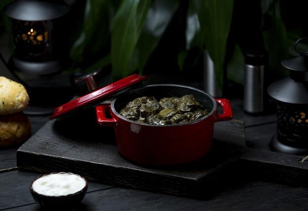 Una olla roja de comida local yarpaq dolmasi, sarma en un tablero oscuro