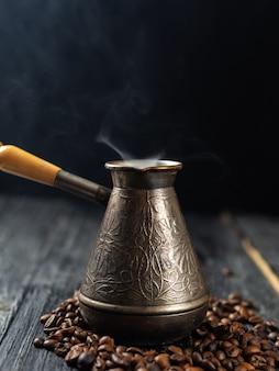 Ollas con café recién hecho sobre un fondo oscuro con humo