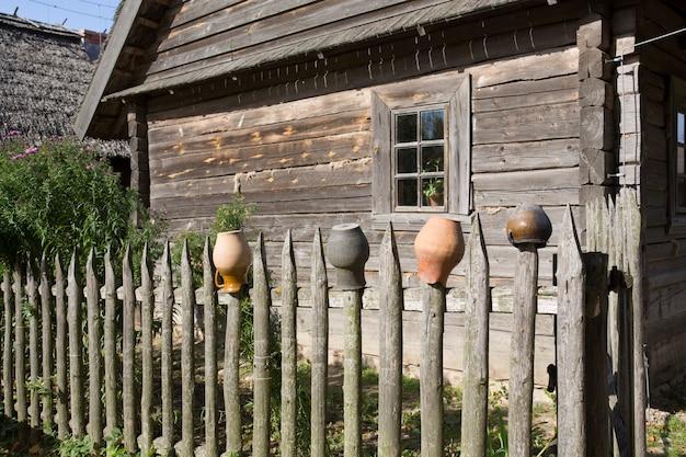 Ollas para estufa de leña rústica, secar sobre empalizada de madera rústica. en el contexto de una vieja casa de madera. foto de alta calidad