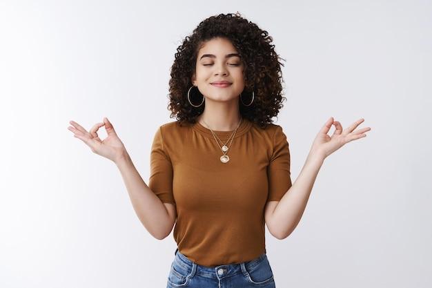 Om girl siente paz, paciencia. atractivo, despreocupado, relajado, feliz, mujer joven, rizado, camisa, peinado, ojos cerrados, sonriente, encantado, meditando, manos, de lado, nirvana, loto, postura, respiración, práctica, yoga