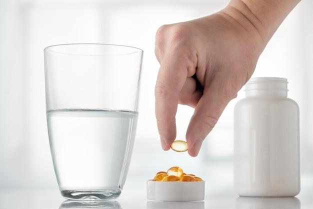 Omega 3, grasa de pescado, aminoácidos y un vaso de agua sobre la mesa.