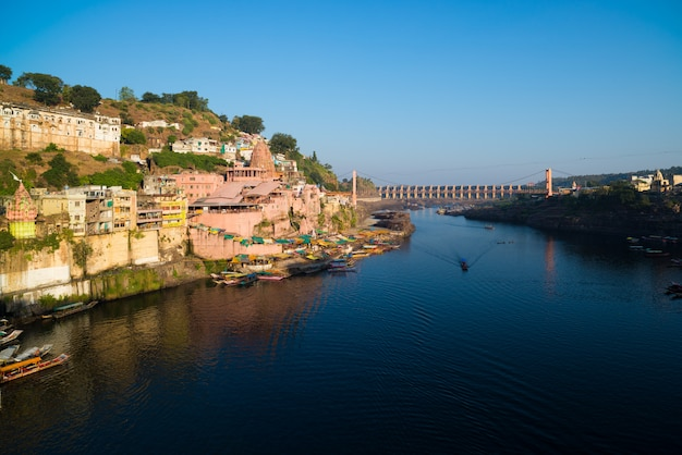 Omkareshwar paisaje urbano, india, sagrado templo hindú. santo río narmada, barcos flotando.