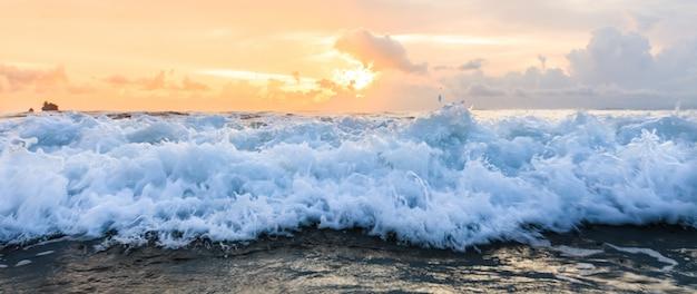 Onda de agua de mar cerca con fondo de cielo sunse
