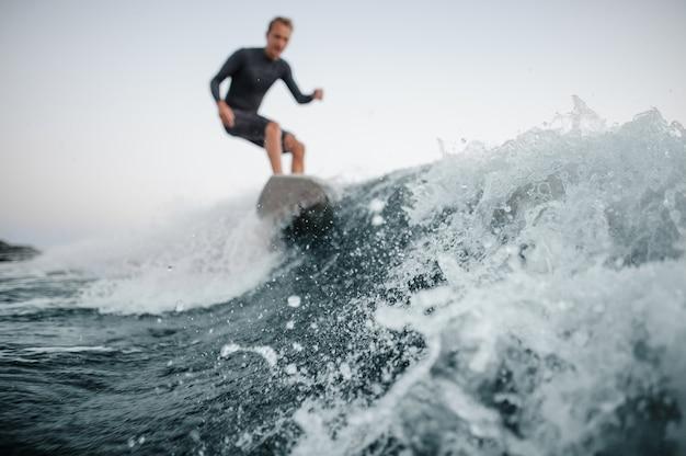 Onda azul en foco en primer plano con un hombre wakesurfing