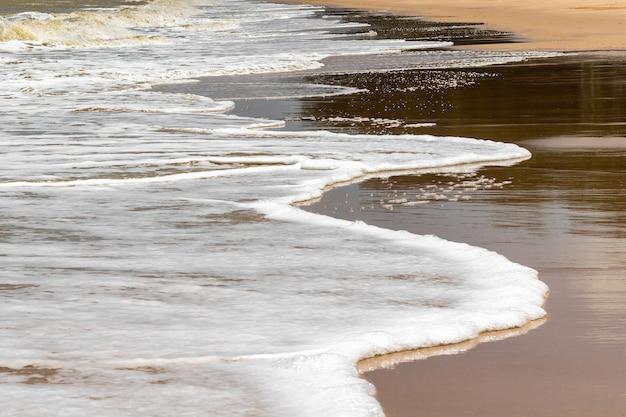 Onda suave del mar en la playa de arena
