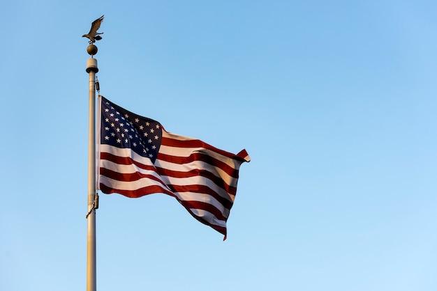 Ondeando la bandera americana contra el cielo azul, ondeando la bandera de estados unidos
